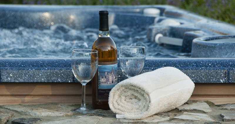 wine glasses next to a hot tub